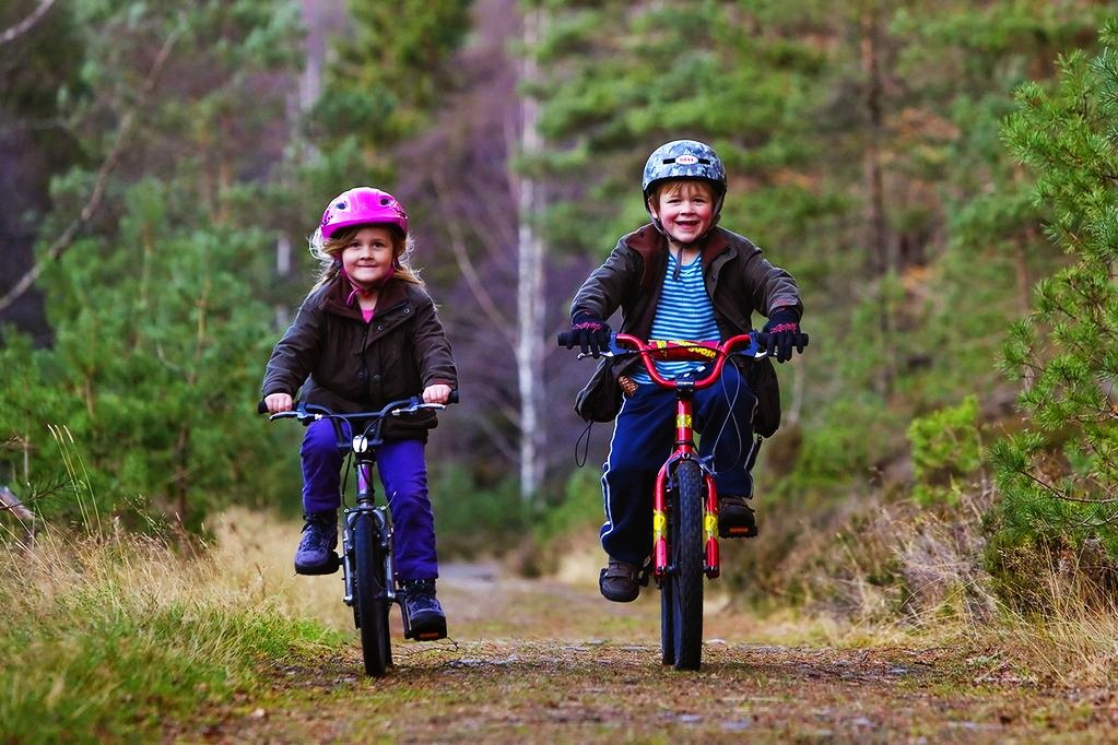 Children riding bikes, Inshriach Forest, Cairngorms National Park, Scotland