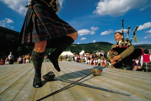 A PARTICIPANT TAKES PART IN THE SWORD DANCING EVENT WHILST A PIPER PROVIDES THE MUSICAL ACCOMPANIMENT AT THE BALLATER HIGHLAND GAMES, BALLATER- A VILLAGE ON THE RIVER DEE, EAST OF BRAEMAR, ABERDEENSHIRE. PIC: VisitScotland