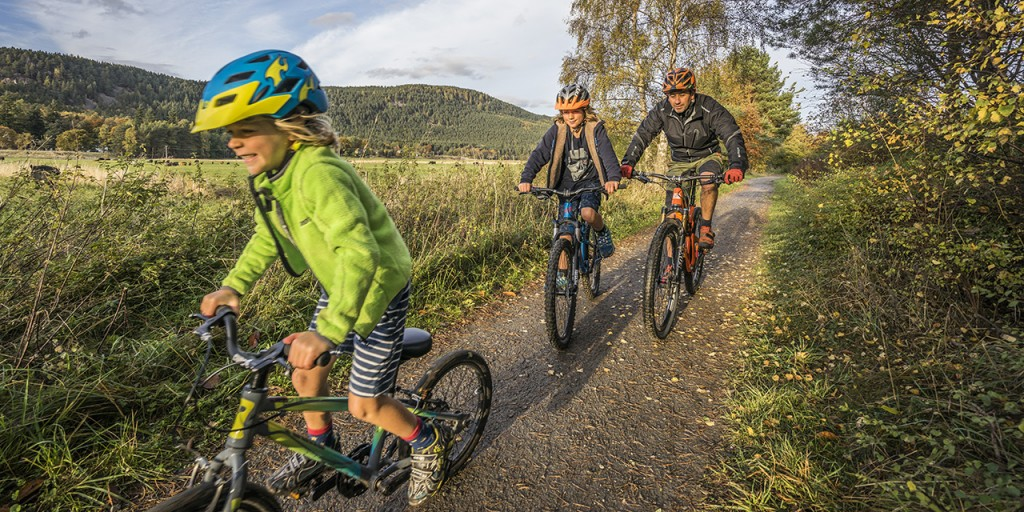 A family of cyclists follow the Deeside country paths during the fall, The Cairngorms National Park.